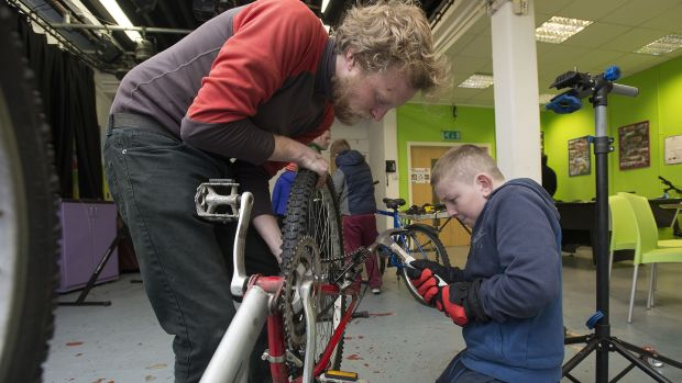Bike mechanic Barry Semple working on a bike with Martin at Bradog Youth Service. Photograph: Dave Meehan