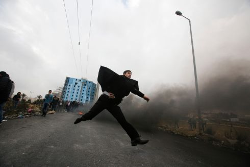 MIDDLE EAST PROTESTS A Palestinian lawyer hurls stones towards Israeli troops during clashes in Ramallah. Photograph: Nasser Shiyoukhi/AP Photo