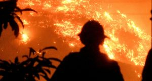 Firefighters watch the Thomas wildfire in the hills outside Montecito, California, on Saturday. Photograph: Reuters