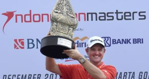 Justin Rose of England celebrates with the trophy after winning the Indonesian Masters golf tournament in Jakarta. Photo: Getty Images