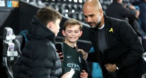 Manchester City's Catalan manager Pep Guardiola takes a picture with a young fan. Photograph: PA