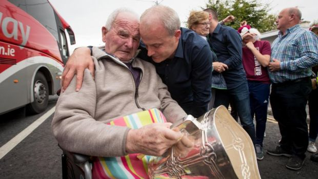 Micheál Donoghue shares an emotional moment with his father as he presents him with the Liam MacCarthy cup. Photo: Morgan Treacy/Inpho