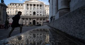 A pedestrian walks over a puddle reflecting the Bank of England (BoE) in the City of London Photographer: Chris J. Ratcliffe/Bloomberg