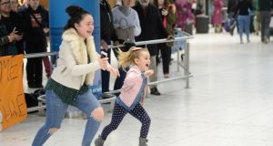 Jamie Crosbie (17) and Katie Crosbie (6), from Tallaght, run to welcome their sister Ciara, arriving home for Christmas, from Sydney. Photograph: Dara Mac Dónaill