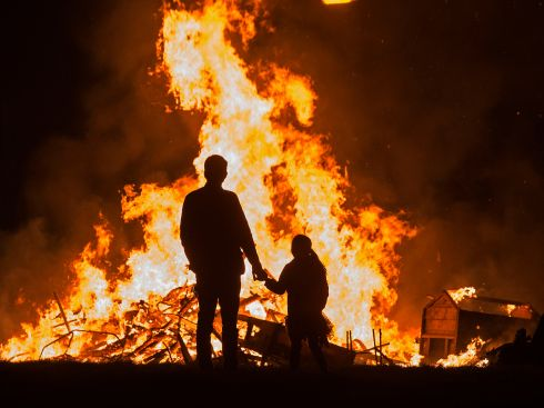 A man watches a bonfire with his daughter in Jobstown, Tallaght on Halloween night. Photograph: Dave Meehan/The Irish Times