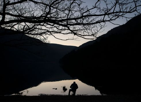 A photographer sets up a shot at dusk at the upper lake in Glendalough Co Wickow. Photograph: Dave Meehan