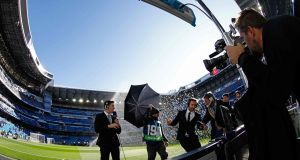 Journalists get wet pitchside ahead of Real Madrid CF vs FC Barcelona at the Santiago Bernabeu stadium. Photograph: Getty Images