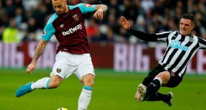 West Ham's  Marko Arnautovic scores the opening goal despite a challenge from Newcastle United's  Ciaran Clark during the Premier League game at   The London Stadium. Photograph: Ian Kington/AFP/Getty Images