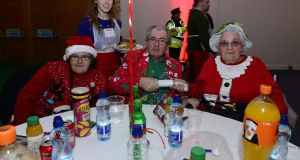 Eimear Larkin from Celbridge helping to serve Maria Byrne, James Byrne and Kathleen Byrne all from Dublin 7 at the Knights of St Columbanus Christmas dinner at the RDS. Photograph: Cyril Byrne/The Irish Times