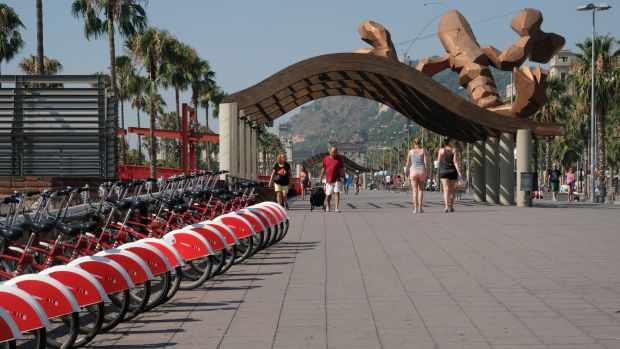 People walk under a sculpture by Spanish artist Javier Mariscal titled 'Giant lobster' near a bicycles for hire station by the marina in Port Vell on July 12, 2017 in Barcelona, Spain. Port Vell or 'Old Harbor' is a waterfront harbor and part of the Port of Barcelona. It was built as part of an urban renewal program prior to the 1992 Barcelona Olympics. Before this, it was a run-down area of empty warehouses, railroad yards, and factories. Photograph: Kaveh Kazemi/Getty Images