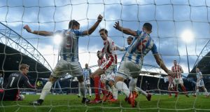 Peter Crouch of Stoke City shoots but has the ball played off the line by Chris Lowe and Jonathan Hogg. Photograph: Gareth Copley/Getty Images