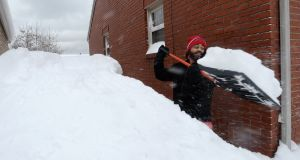 Patrick Harden clears snow from the roof of his car on Tuesday in Erie, Pennsylvania. Photograph: Greg Wohlford/Erie Times-News via AP