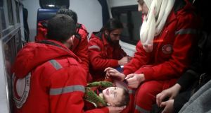 Syrian Red Crescent Syrian staff evacuate a babyfrom the eastern Ghouta district on the outskirts of Damascus. Photograph: Abdulmonam Eassa/AFP/Getty Images