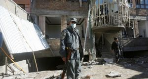 An Afghan policeman keeps watch at the site of the suicide attack in Kabul. Photograph: Reuters