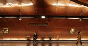 Commuters wait on a platform at the metro station Arts et Metiers, which is covered with copper panels, in Paris. Photograph: Gonzalo Fuentes/Reuters
