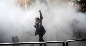A woman raises her fist amid tear gas at the University of Tehran during a protest on December 30th, 2017. Photograph: STR/AFP/Getty Images