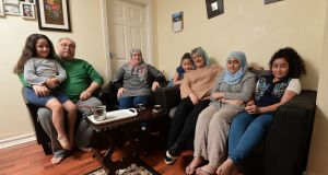 From left: Aya with her dad Feras, mother Nabeha, Fatima, Brenda Gough (family friend), Mona and Sedra at their west Belfast home. Photograph: Colm Lenaghan/Pacemaker