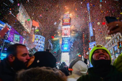 People celebrate New Year as confetti falls after the countdown to midnight in Times Square during New Year's celebrations, Monday, Jan. 1, 2018, in New York. (AP Photo/Go Nakamura)