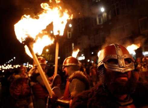 Up Helly Aa vikings from the Shetland Islands hold lit torches during the annual torchlight procession to mark the start of Hogmanay (New Year) celebrations in Edinburgh, Scotland December 30, 2017.  REUTERS/Russell Cheyne