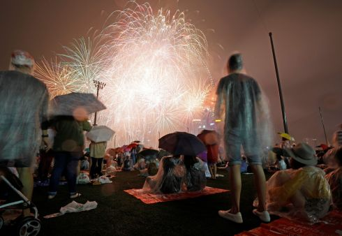 People watch fireworks in the rain ahead of the New Year at Marina Bay in Singapore December 31, 2017. REUTERS/Edgar Su
