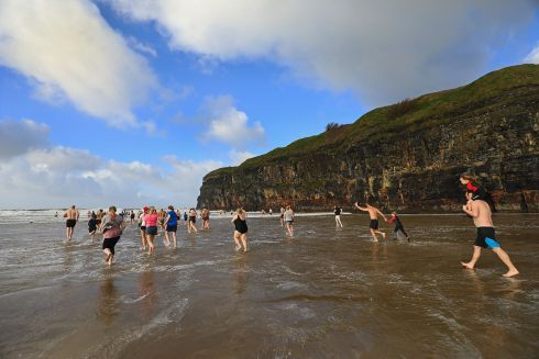 GOOD TIDINGS: Swimmers take a dip on Ballybunion Strand, in aid of the cardiology unit of Our Lady's Children's Hospital, Crumlin. Photograph: Valerie O'Sullivan