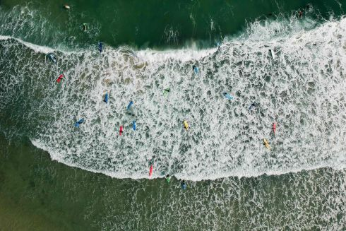 TAKE ON BOARD: People paddle out as waves break at a beach in Hong Kong. Photograph: AFP/Getty Images