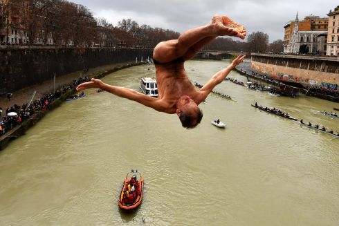HIGH JUMP: Marco Fois dives into the Tiber river as part of new year celebrations in Rome, Italy. Photograph: Alberto Pizzoli/AFP/Getty Images