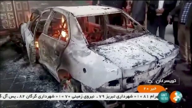 People stand near a burning car in Tuyserkan, Hamadan Province, Iran, December 31, 2017 in this still image taken from video. Photograph: IRINN/ReutersTV via Reuters