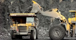 A digger loads large rocks from the pit floor onto a truck at a CRH  quarry.  Photograph: John Cogill/Bloomberg News