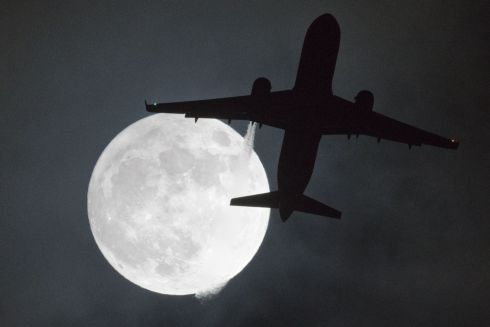"Supermoons, such as last nights Jan 1st, happen when a full moon approximately coincides with the moon's perigee, or a point in its orbit at which it is closest to Earth - a plane flys in front of a ""super moon"" or ""wolf moon"" on its approach to London Heathrow Airport on January 1st.  Photograph: Justin Tallis / AFP"