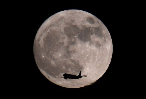 A passenger plane, with a 'supermoon' full moon seen behind, makes its final landing approach towards Heathrow Airport in London. Photograph: Toby Melville / Reuters