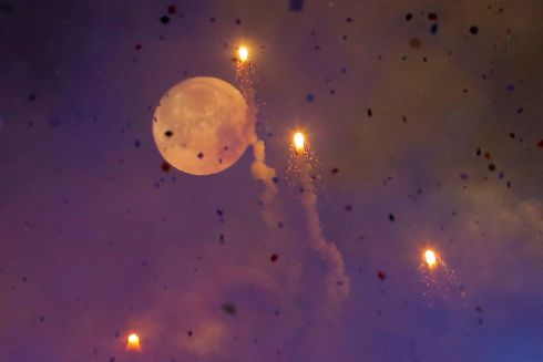 The moon is seen through fireworks over Times Square during New Year's celebrations in Manhattan.  Photograph: Andrew Kelly / Reuters