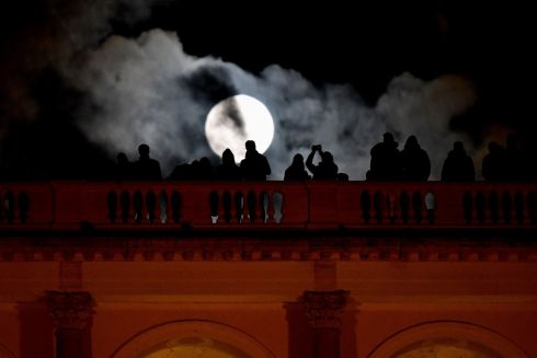 "People admires the ""super moon"" from the Terrazza del Pincio, in Rome. Photograph:  Alberto Pizzoli / AFP"