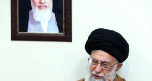 Iranian Supreme leader Ayatollah Ali Khamenei, sitting under a portrait of the late Iranian revolutionary founder Ayatollah Khomeini, as he speaks during a meeting with family members of Iranian martyrs, in Tehran yesterday. Photograph: EPA