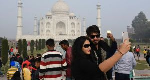Visitors take  selfies in front of the Taj Mahal in Agra, India, today. India is to restrict the number of daily visitors to the 17th century monument  in an effort to preserve it. Photograph: Dominique Faget/AFP/Getty Images