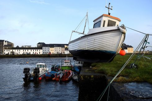 A boat is stranded on the edge of a pier after it was washed aground by floods in Galway. Photograph: Clodagh Kilcoyne/Reuters