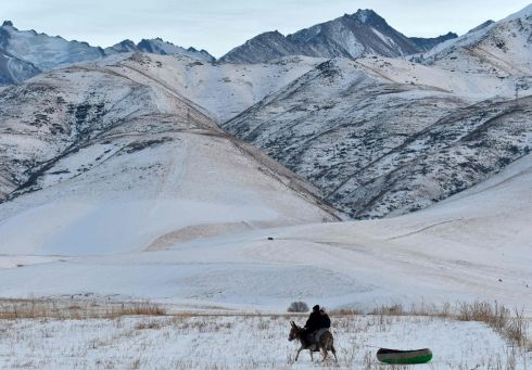 Two boys ride a donkey towing an inflatable raft on a snow-covered path near the village of Kyzyl Birlik, some 25km from Bishkek, Kyrgyzstan. Photograph: Getty Images