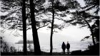 The calm after the storm: Walkers look out at a high swell on Lough Leane near Ross Castle in Killarney on Wednesday. Photograph: Bryan O'Brien
