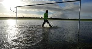 Groundsman for West Untied FC Keith Devlin, inspects their waterlogged pitch after Storm Eleanor wreaked havoc in the area. Photograph: Ray Ryan