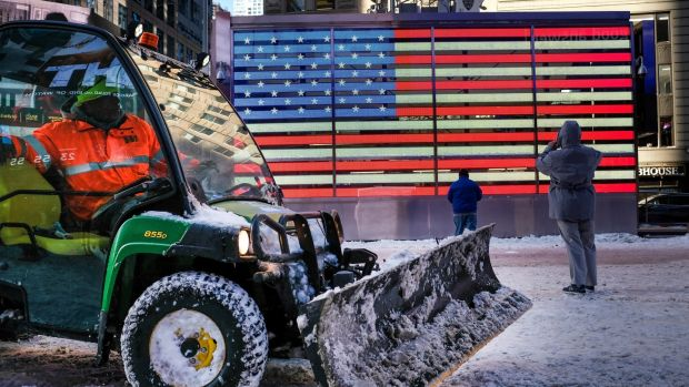 A worker spreads road salt and plows snow in a plaza in Times Square on Friday. Photograph: Drew Angerer/Getty Images