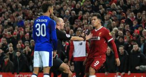 Everton's Mason Holgate and Liverpool's Roberto Firmino clash during the FA Cup third round match at Anfield. Photo: Peter Byrne/PA Wire