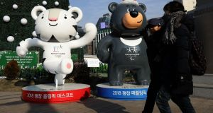 People walk past the mascots of the 2018 PyeongChang Winter Olympic and Paralympic Games, Soohorang and Bandabi, in Seoul, South Korea. Photograph: Chung Sung-jun/Getty Images