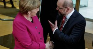 Martin Schulz (R), head of the German Social Democrats (SPD), welcomes German chancellor Angela Merkel at the headquarters of the SPD for preliminary coalition talks. Photograph: Carsten Koall/Getty Images