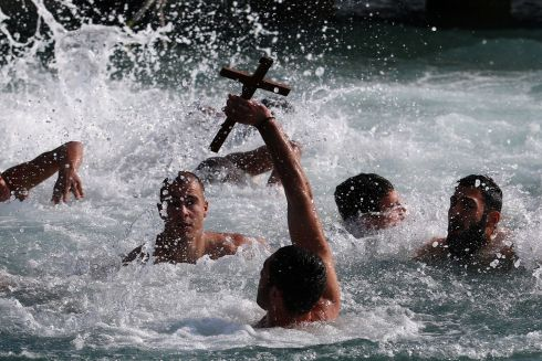 A man holds a cross during a competition to retrieve it from the water during Epiphany day celebrations in the port village of Zygi, near Limassol, Cyprus. Photograph: Reuters