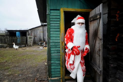 A man dressed as Father Frost leaves a house as he celebrates the traditional Kalyady holiday in the village of Sredniye Pechi, some 290 km south of Minsk, Belarus. Photograph: Getty Images