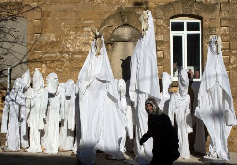 An elderly woman walks in front of puppets covered with white sheets, placed in a street in Camlica Village prior the 'Bocuk Festival' in Kesan district of Edirne city, Turkey. Residents dress in white sheets and paint their faces to spook people as ghosts during the Bocuk festival, a medieval Thracian Haloween. Photograph: EPA