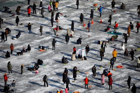 People fish for trout on a frozen river during the Ice Festival in Hwacheon, south of the demilitarised zone separating the two Koreas. Photograph: Reuters