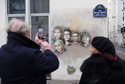 A man takes a picture of portraits (from left) of late French satirical weekly Charlie Hebdo's deputy chief editor Bernard Maris, French cartoonists Georges Wolinski, Bernard Verlhac (aka Tignous), Charlie Hebdo editor Stephane Charbonnier (aka Charb) and Jean Cabut (aka Cabu) near the magazine's offices at Rue Nicolas Appert, in Paris. Photograph: Getty Images