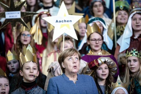 IN HARMONY: German chancellor Angela Merkel sings with children during a welcome reception for carol singers, so-called 'Sternsinger' at the Chancellery in Berlin. Photograph: Till Rimmele/EPA