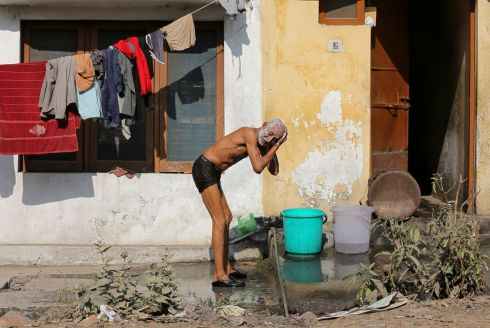 COOLING OFF: A man applies soap on his head as he bathes at a marketplace in Jammu, India. Photograph: Mukesh Gupta/Reuters